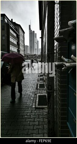 Man Walking Under Umbrella On Cobblestone Street - Stock Photo