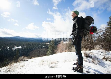 Young male hiker looking out from snow covered landscape, Ashland, Oregon, USA - Stock Photo