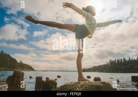 Ballet dancing girl poised on rock, Bainbridge Island, Washington State, USA - Stock Photo