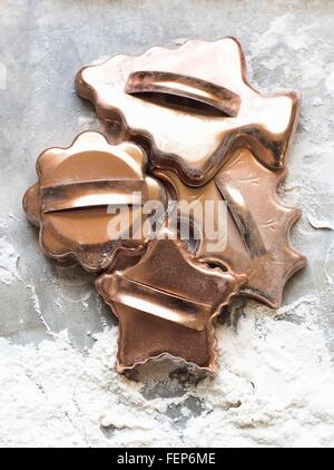 Overhead view of selection of gold colour Christmas cookie cutters - Stock Photo