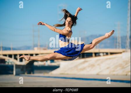 Side view of young woman doing the splits in mid air looking at camera smiling, Los Angeles, California, USA - Stock Photo