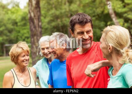 Group of adults outdoors, wearing sports clothing, smiling - Stock Photo