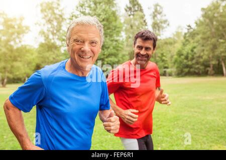 Two men running outdoors, smiling - Stock Photo