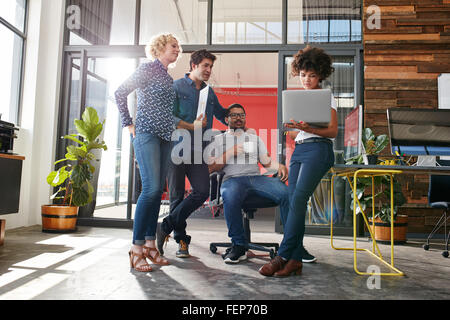 Multiracial group of designers meeting in modern office discussing work. Young entrepreneurs having a meeting for - Stock Photo