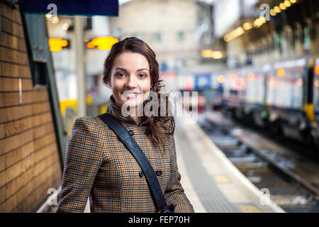 Young woman in brown winter coat waiting on train station - Stock Photo