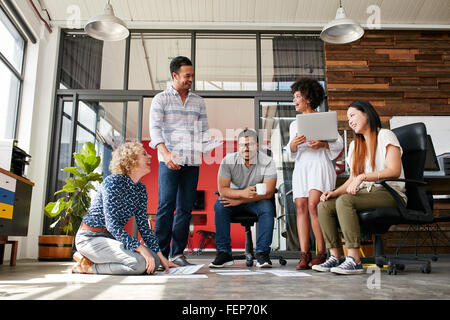 Group of creative people discussing new project. Woman sitting with documents laid on floor and smiling while having - Stock Photo