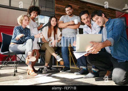 Startup team working and planning in the meeting. Group of young men and women looking at laptop at office. - Stock Photo