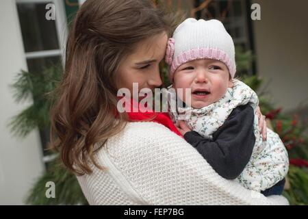 Young girl, crying, being consoled by mother, outdoors - Stock Photo