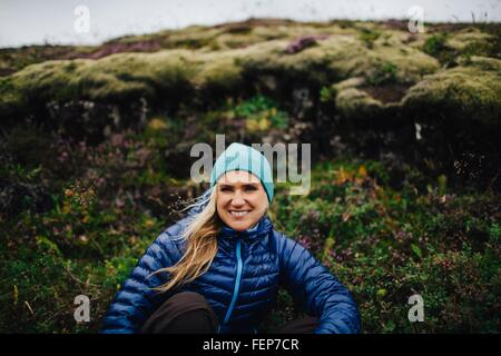 Front view of mid adult woman crouched in front of mound wearing knit hat looking at camera smiling, Iceland - Stock Photo