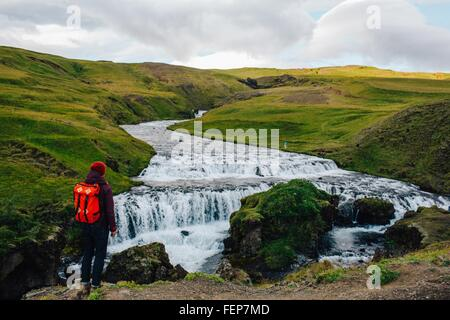 Rear view of mid adult man looking at river flowing through lush green landscape, Iceland - Stock Photo