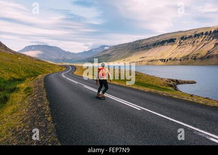 Rear view of mid adult man skateboarding on curving open road by lake, Iceland - Stock Photo