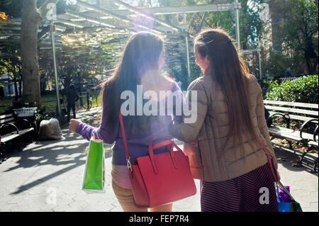 Rear view of young female adult twins strolling in park with shopping bags - Stock Photo
