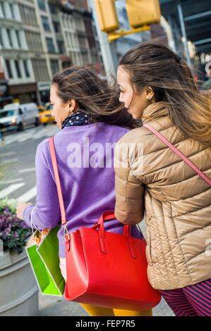 Rear view of young female adult twins looking sideway to cross city road - Stock Photo