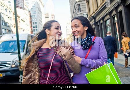 Young female adult twins with shopping bags strolling and chatting on city street - Stock Photo