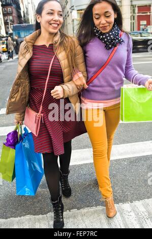 Young female adult twins with shopping bags crossing city road - Stock Photo