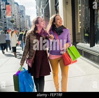 Young female adult twins carrying shopping bags strolling and chatting on city sidewalk - Stock Photo