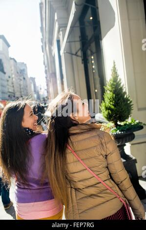 Rear view of young female adult twins window shopping in city - Stock Photo