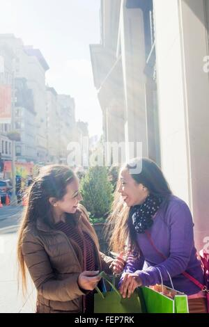 Young female adult twins with shopping bags chatting and laughing on city sidewalk - Stock Photo