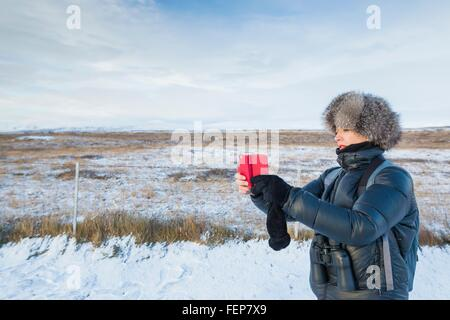 Mature woman taking photograph on snow-covered field, Iceland - Stock Photo