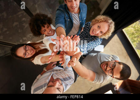 Top view of successful team of professionals high fiving and looking at camera smiling. Men and women making a pile - Stock Photo