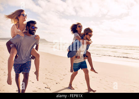 Two beautiful young couples walking by the beach, with men carrying their women on their back. Couples piggybacking - Stock Photo