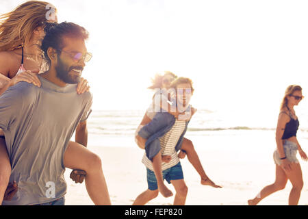 Group of friends having fun on the beach, Young men piggybacking women on the sea shore. Mixed race young people - Stock Photo