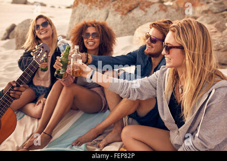 Young people sitting together at beach and having a party. Group of friends cheers with beers at the beach. - Stock Photo