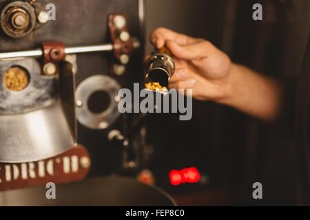 Man putting coffee beans into coffee roaster, close-up - Stock Photo