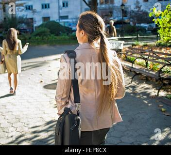 Rear view of young women walking through city park - Stock Photo