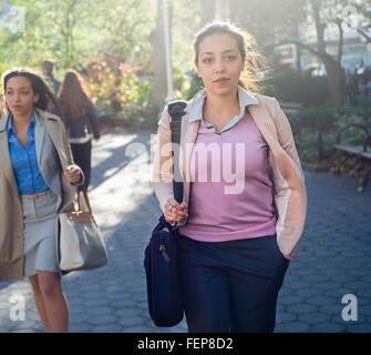 Young woman walking through city park - Stock Photo