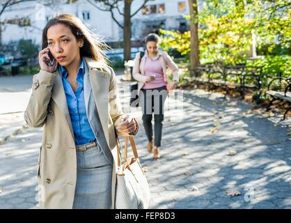Young woman chatting on smartphone whilst walking through city park - Stock Photo