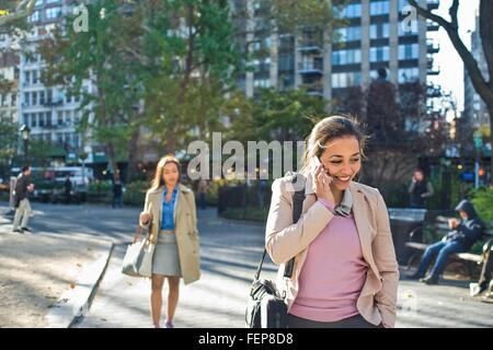 Young woman talking on smartphone whilst walking through city park - Stock Photo
