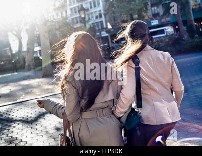 Rear view of young adult female twins walking through city park - Stock Photo