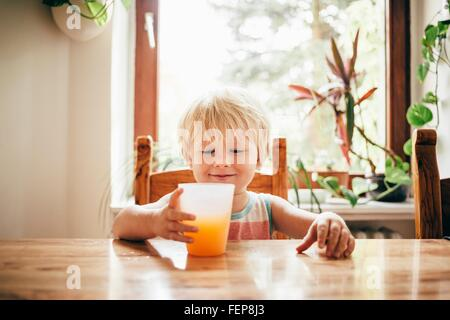 Boy sitting at table with beaker of orange juice looking down smiling - Stock Photo