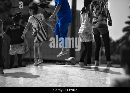 Low Section Of Children Jumping On Floor - Stock Photo