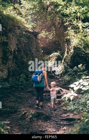 Full length rear view of mother and sons hiking up trail, looking over shoulder at camera smiling, Bludenz, Vorarlberg, - Stock Photo
