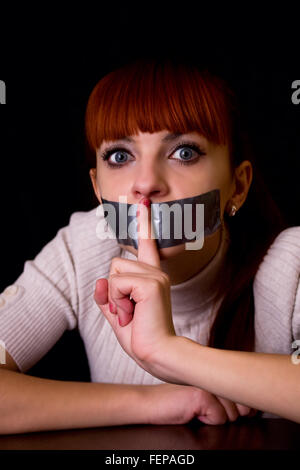 girl with her mouth sealed with tape brought finger to his mouth calling silent - Stock Photo
