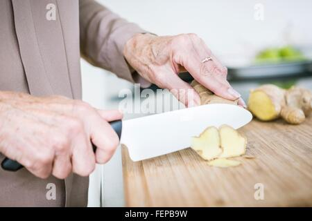 Close up of senior female hands chopping ginger - Stock Photo