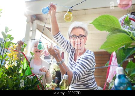 Two women in garden, hanging colourful lights - Stock Photo
