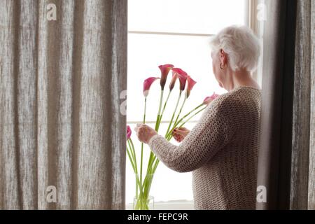 Senior woman arranging flowers in vase, rear view - Stock Photo