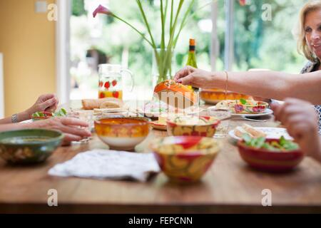 Three women having lunch together at home - Stock Photo