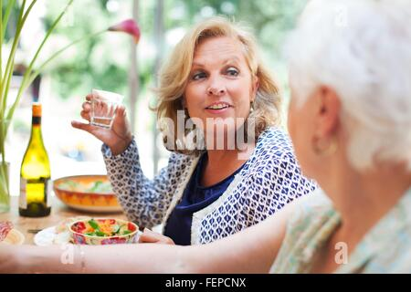 Two women having lunch together at home - Stock Photo