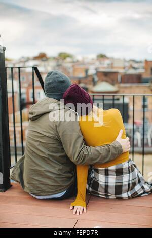Young couple sitting looking out from city rooftop terrace - Stock Photo