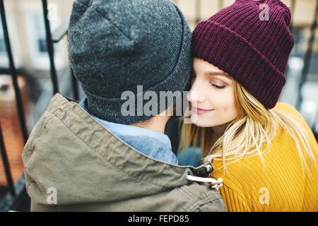 Romantic young couple wearing knitted hats sitting on stairway - Stock Photo