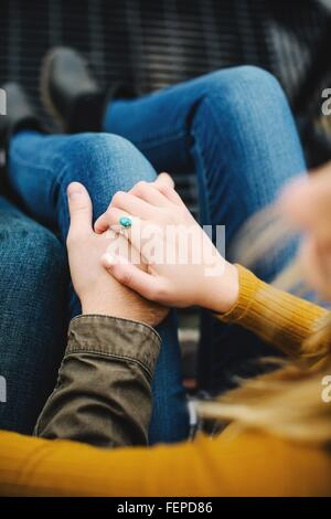 Over shoulder cropped shot of young couple holding hands on stairway - Stock Photo