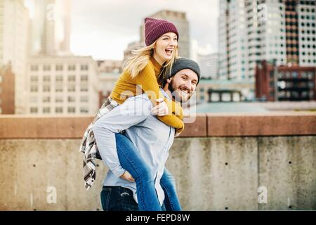 Young man giving girlfriend a piggyback on city rooftop terrace - Stock Photo