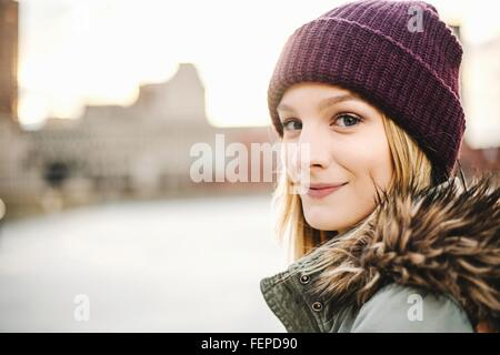 Portrait of young woman wearing knitted hat and fur hood - Stock Photo