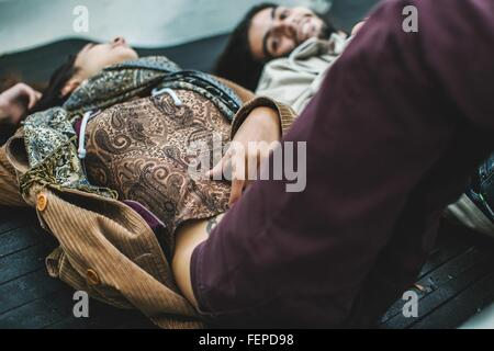 Young couple lying in back of truck - Stock Photo