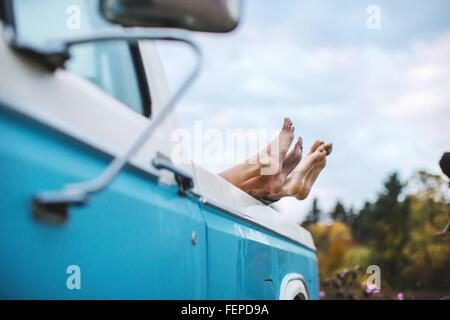 Young couple lying in back of truck, bare feet on edge of truck, focus on feet - Stock Photo