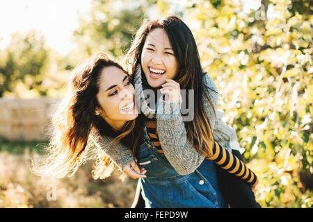 Young woman giving friend piggyback ride, outdoors - Stock Photo